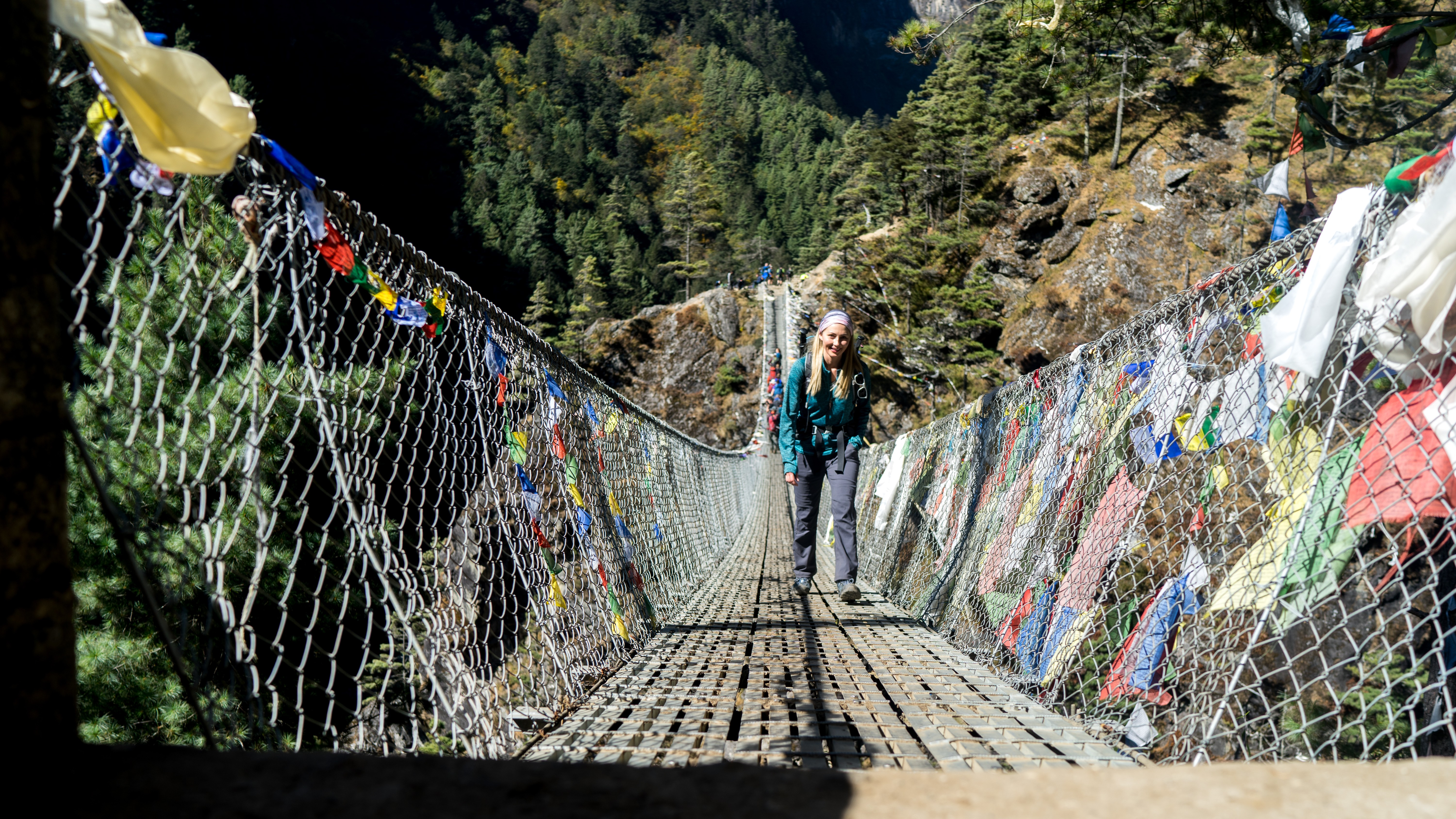 Female trekker on a suspension bridge to EBC